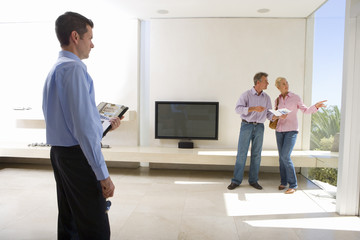Male real estate agent looking at mature couple standing in living room