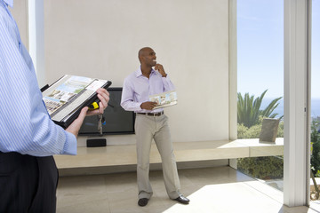 Man standing in living room of house, smiling, male real estate agent in foreground