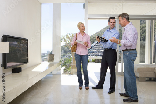 Male real estate agent standing with mature couple in living room, smiling