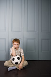 grumpy little boy sitting on floor with football