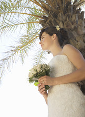 A bride standing beneath a palm tree
