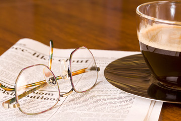 Coffee newspaper and reading glasses