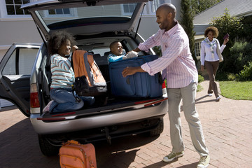 Son and daughter (6-10) helping father load luggage in back of car (tilt)