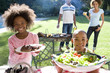 Family of four having barbeque, portrait of brother and sister (6-10) smiling