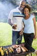 Man embracing woman by barbeque, smiling, portrait