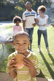 Boy (6-8) eating burger, family at barbeque in background, smiling, portrait