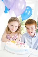 two children sitting at table with birthday cake