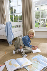 Boy (6-8) in bedroom drawing, smiling, portrait