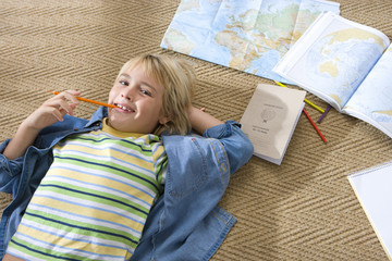 Boy (6-8) lying on floor by maps, pencil in mouth, smiling, portrait, elevated view