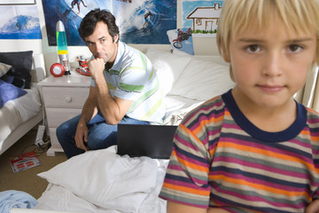 Father on bed looking at son (6-8), close-up of boy (differential focus)