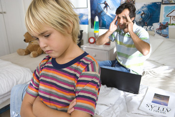Father reprimanding son (6-8) in bedroom, close-up of boy