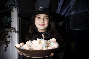 Girl in a witch's costume at a Hallowe'en party, holding a tray of sweets