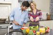 Man and woman making salad, smiling