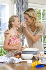 Mother and daughter (8-10) baking, mother touching daughter's nose, smiling