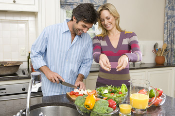 Man and woman making salad, smiling