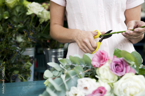 Woman's hands tying together a bouquet of pink and white roses