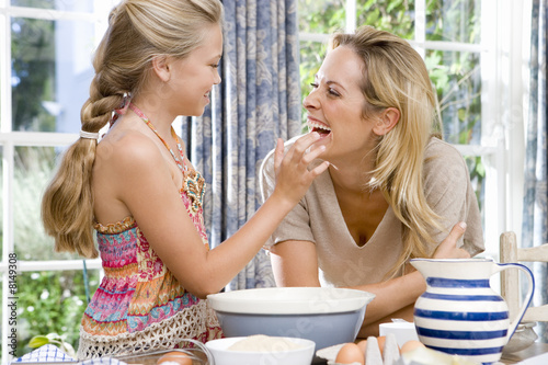 Mother and daughter (8-10) baking, smiling at each other, side view