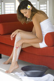 Young woman in bath towel on sofa shaving legs, side view