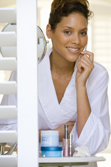 Young woman in bathrobe, smiling, portrait, view through shutters