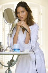 Young woman in bathrobe with hairdryer, leaning on table by mirror, portrait