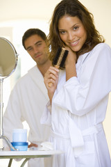 Young couple in bathrobes, woman with hairbrush, smiling, portrait (differential focus)