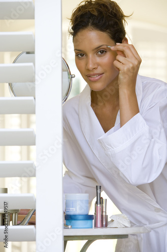 Woman in bathrobe plucking eyebrows, portrait, view through shutters