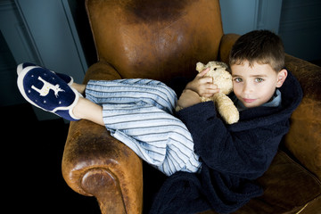 little boy getting cosy in armchair with teddy bear
