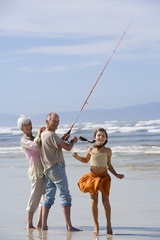 Girl (7-9) by grandparents fishing on beach, smiling, portrait