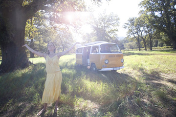 Young woman with arms outstretched by camper van in field (lens flare)
