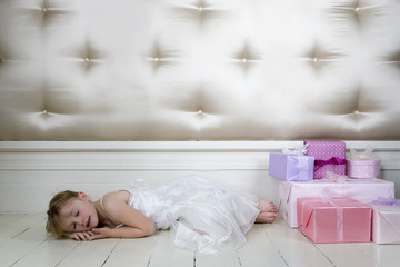 Little girl asleep on the floor next to her birthday presents
