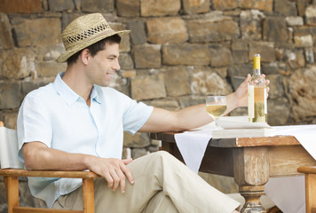 A man drinking a glass of wine