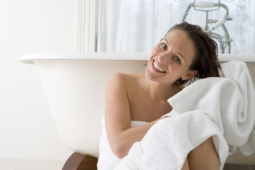 Young woman in bath towel drying hair with towel by bath, smiling, portrait