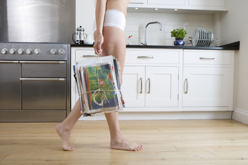 Young woman in underwear carrying newspaper bundle in kitchen, low section