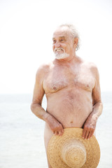 Naked senior man covering himself up with a straw hat