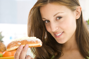 Young woman with cream roll, smiling, portrait, close-up