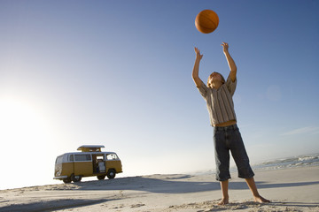 Boy (6-8) on beach throwing ball up, camper van in background, low angle view