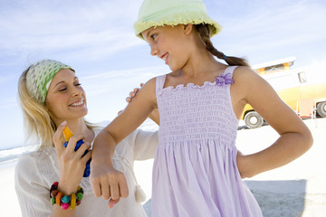 Mother applying sunscreen to daughter (5-7) on beach, smiling, low angle view