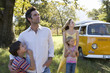 Parents embracing son and daughter (5-9) in field by camper van, low angle view