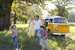 Family of four in field by camper van, son and daughter running (5-9), smiling