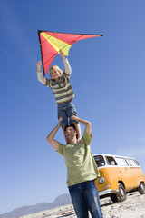 Boy (6-8) standing on father's shoulders with kite on beach, camper van in background, low angle view