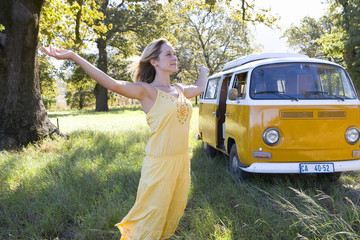Young woman with arms outstretched in field by camper van, low angle view