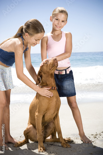 Two young girls and a dog on the beach