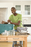 Young man putting empty glass jar and can into recycling bin in kitchen, smiling, portrait