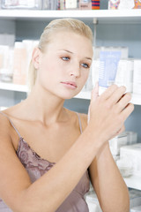 Woman choosing moisturising cream at the cosmetics counter