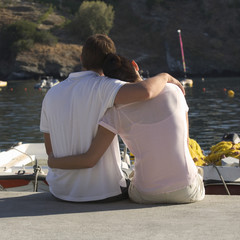 A couple sitting by a harbour