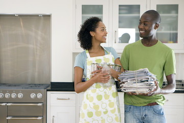 Young couple with recycling in kitchen, smiling at each other