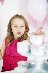 girl in taking cake from cake stand at birthday party