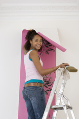 Young woman on ladder putting up wallpaper, smiling, portrait