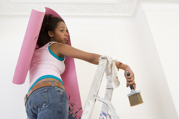Young woman on ladder putting up wallpaper, low angle view