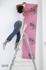 Woman hanging wallpaper from step ladder.